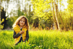Happy child girl in yellow vest walking in summer sunny forest. Kids exploring nature. Cozy rural scene Stock Photos