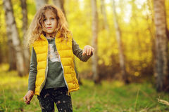 Happy child girl in yellow vest walking in summer sunny forest. Kids exploring nature. Cozy rural scene Stock Photography
