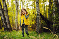 Happy child girl in yellow vest walking in summer sunny forest Royalty Free Stock Images