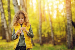 Happy child girl in yellow vest walking in summer sunny forest. Kids exploring nature. Cozy rural scene Stock Photo