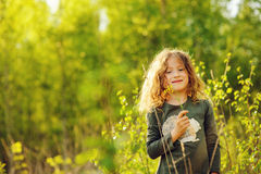 Happy child girl in yellow vest walking in summer sunny forest Stock Photography
