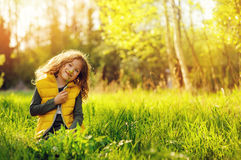 Happy child girl in yellow vest walking in summer sunny forest Royalty Free Stock Photo