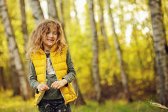Happy child girl in yellow vest walking in summer sunny forest Stock Images
