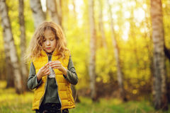 Happy child girl in yellow vest walking in summer sunny forest Royalty Free Stock Photos