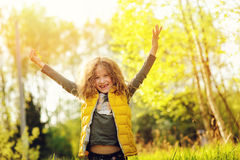 Happy child girl in yellow vest walking in summer sunny forest. Kids exploring nature. Cozy rural scene Stock Image
