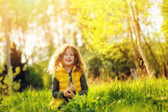 Happy child girl in yellow vest walking in summer sunny forest. Kids exploring nature. Cozy rural scene Royalty Free Stock Photos