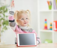 Happy child in glasses with hand up and tablet pc Royalty Free Stock Images