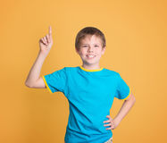 Happy child with good idea holds finger up isolated on yellow ba stock photos