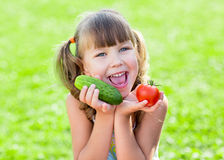 Happy child on grass loan with healthy vegetables Stock Images
