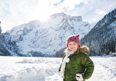 Happy child in green coat standing in front of snowy mountains Stock Photo