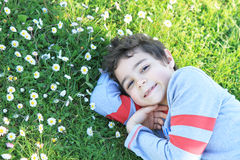 Happy child on the green grass. Happy and smilling boy  on the green grass Royalty Free Stock Photo