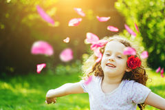 Happy child hand up, enjoying freedom with flying flower petals Royalty Free Stock Photo