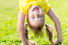Happy child has fun standing head down on green Royalty Free Stock Photos