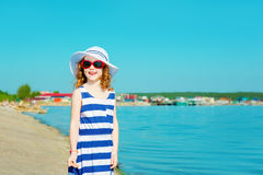 Happy child in a hat and sunglasses in the sea. Travel and vacat Stock Image