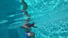 Happy child having fun in blue clear pool. With sun rays reflections in the water stock footage