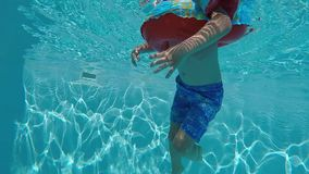 Happy child having fun in blue clear pool. Happy child swimming in blue clear pool with sun rays reflections in the water stock video footage