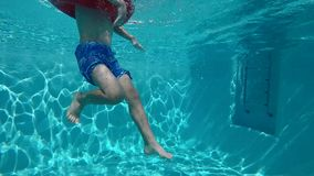 Happy child having fun in blue clear pool. Happy child swimming in blue clear pool with sun rays reflections in the water stock footage