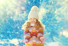 Happy child having fun playing with snow in winter Royalty Free Stock Image