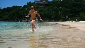 The happy child having fun runs on the shore of a tropical sea stock video footage