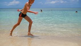 The happy child having fun runs on the shore of a tropical sea stock video