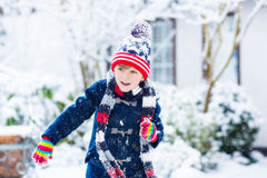 Happy child having fun with snow in winter Stock Images