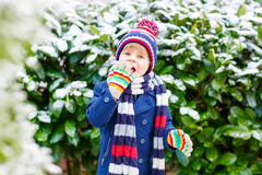 Happy child having fun with snow in winter Royalty Free Stock Photo