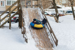 Happy child is heading to ice mountain for tubing in the winter Royalty Free Stock Photography