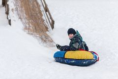Happy child is heading to ice mountain for tubing in the winter Stock Photos