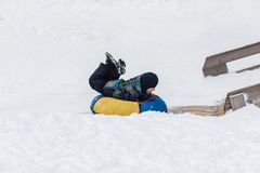Happy child is heading to ice mountain for tubing in the winter Stock Image