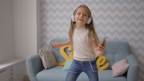 Happy child with headphones and smartphone dancing and listening to music at home stock video