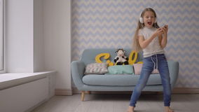 Happy child with headphones and smartphone dancing and listening to music at home stock footage