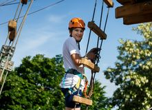 Happy child, healthy teenager school boy in orange helmet enjoys activity in a climbing adventure rope park. On a sunny summer day stock images