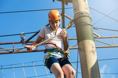 Happy child, healthy teenager school boy in orange helmet enjoys activity in a climbing adventure rope park. On a sunny summer day royalty free stock image