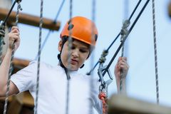 Happy child, healthy teenager school boy in orange helmet enjoys activity in a climbing adventure rope park. On a sunny summer day royalty free stock images