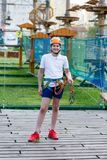 Happy child, healthy teenager school boy in orange helmet enjoys activity in a climbing adventure rope park. On a sunny summer day stock photography