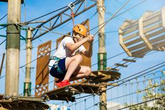 Happy child, healthy teenager school boy in orange helmet enjoys activity in a climbing adventure rope park. On a sunny summer day stock image