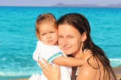 Happy child with her mother on the beach Stock Photo