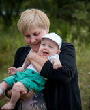 Happy child with his grandmother. Grandmother and her little boy half a year infant baby grandson in outdoors park Royalty Free Stock Images