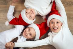 Happy child hold hands and lying on wooden background, dressed in christmas Santa hat and having fun, winter holiday concept Royalty Free Stock Photography