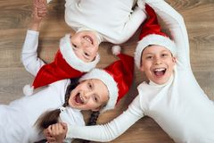 Happy child hold hands and lying on wooden background, dressed in christmas Santa hat and having fun, winter holiday concept Royalty Free Stock Images