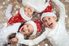 Happy child hold hands and lying on wooden background, dressed in christmas Santa hat and having fun, winter holiday concept, snow Stock Image
