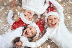 Happy child hold hands and lying on wooden background, dressed in christmas Santa hat and having fun, winter holiday concept, snow. Decoration stock image