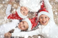 Happy child hold hands and lying on wooden background, dressed in christmas Santa hat and having fun, winter holiday concept, snow Stock Images