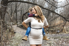Happy child holding belly of pregnant woman in Royalty Free Stock Photography