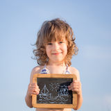 Happy child holding blackboard Royalty Free Stock Photos