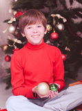 Happy child holding christmas decorations in room Royalty Free Stock Photos