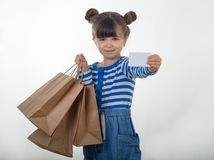 Happy child holding discount white card and shopping bags in her hands. Kid with credit card. Little girl showing empty blank paper note copy space. White stock photos