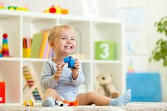 Happy child holding elefant toy. Happy child boy holds elefant toy sitting on floor in nursery royalty free stock image