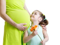 Happy child holding flower looks at pregnant Royalty Free Stock Photos