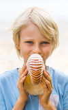 Happy child holding a nautilus shell Stock Photos